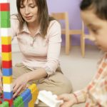 Woman and boy sitting on floor and playing with blocks